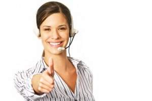 Young friendly female helpdesk operator showing success with thum-up sign